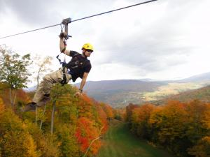 Person ziplining over fall foliage in the Catskills
