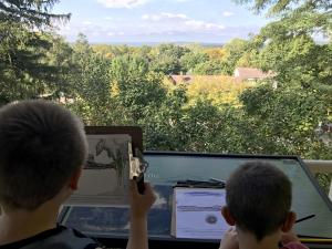 Young learners sketching from Thomas Cole's porch.