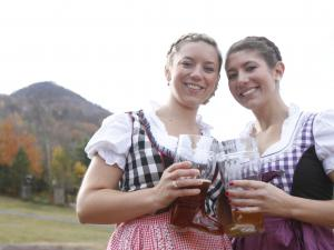 two women clinking beer steins at Oktoberfest at Hunter Mountain