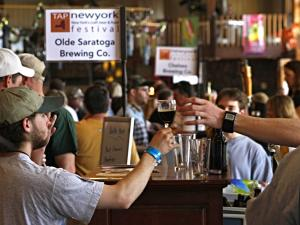 Participants at the TAP NY Craft Beer Festival with an Olde Saratoga Brewing Company sign in the background